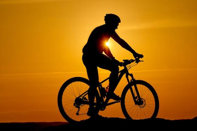 Schattenbild eines sportlichen radfahrers im sturzhelm auf einem fahrrad
