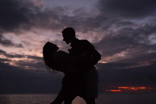 Schattenbild eines tanzenden paares bei sonnenuntergang