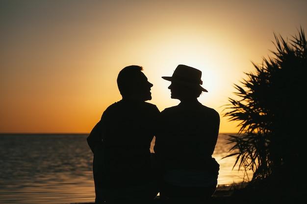 Schattenbild eines verliebten paares an der küste, das einen sonnenuntergang genießt