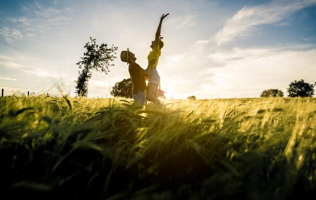 Schattenbild eines verliebten paares, das mit erhobenen armen auf einem weizenfeld bei sonnenuntergang springt.