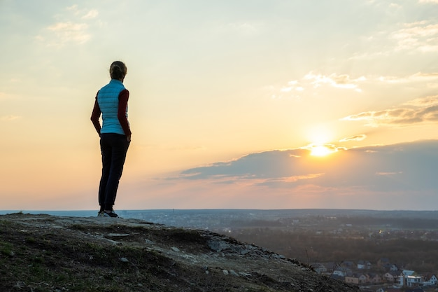 Schattenbild eines wanderers der frau, der allein steht und sonnenuntergang im freien genießt. weiblicher tourist auf ländlichem feld in der abendnatur. konzept für tourismus, reisen und gesunden lebensstil.
