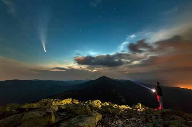 Schattenbild eines wandermannes mit taschenlampe, die auf berggipfel steht. foto des kometen c / 2020 f3 (neowise)