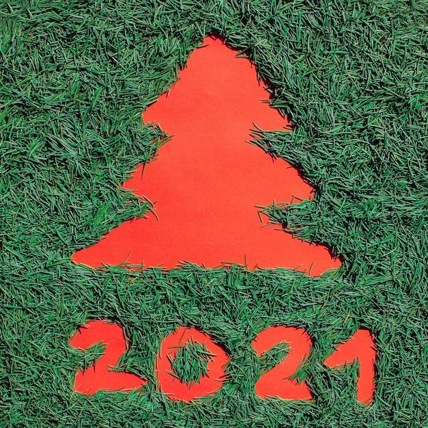 Schattenbild eines weihnachtsbaumes gemacht von den grünen weihnachtsnadeln auf einem roten hintergrund. symbol von 2021.
