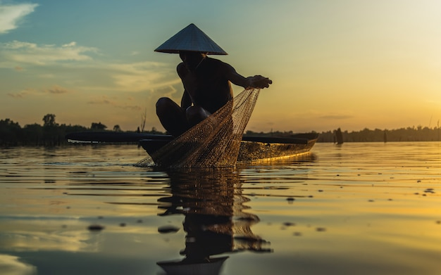 Schattenbild-fischer-fischernetze auf dem boot.