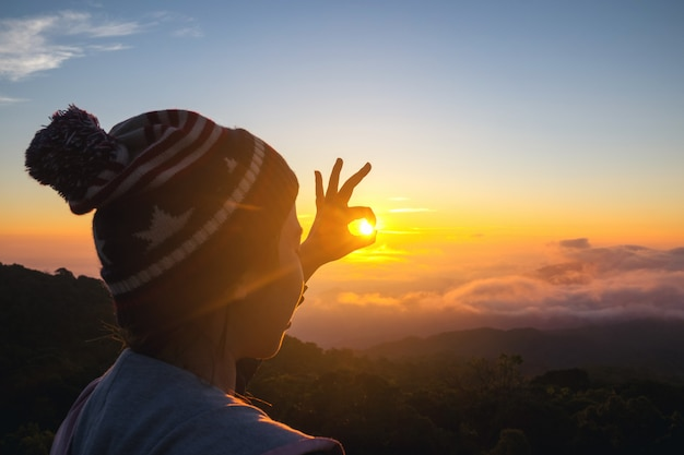 Schattenbild-freiheitsfrau, die mit sonnenuntergang steht und pünktlich genießt