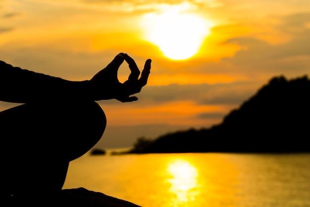 Schattenbild, hand der frau meditierend in der yogahaltung oder lotussitz bei sonnenuntergang