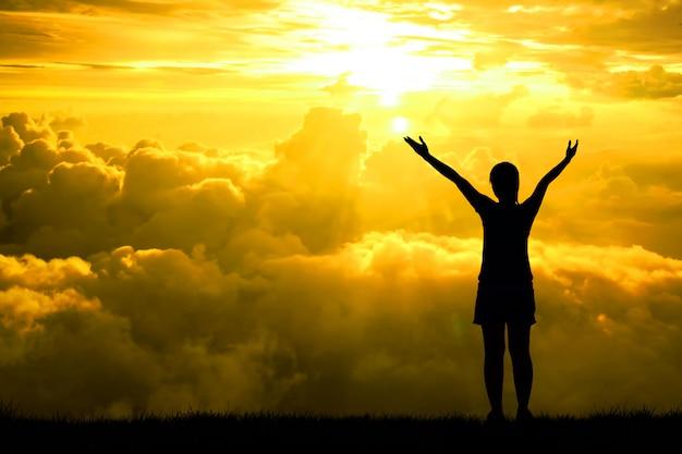 Schattenbild oder hintergrundbeleuchtung von sportfrauen öffnen die arme, die in richtung auf hoffnungshimmel am lichteffekt des sonnenuntergangs angehoben werden. konzept für lebensleistungen und erfolg