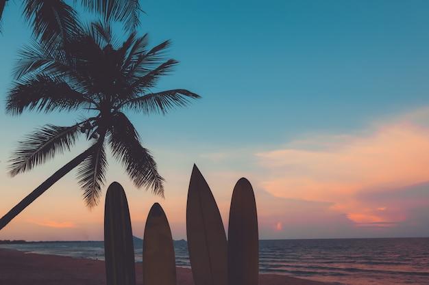 Schattenbild surfbrett auf strand bei sonnenuntergang.