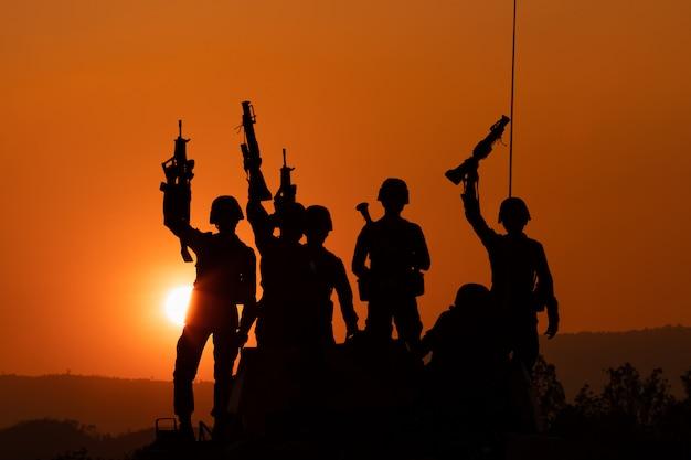 Schattenbild und über dem sonnenaufganghintergrundkanonensoldaten team in thailand