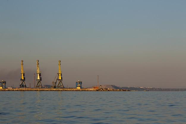 Schattenbild vieler großer kräne im hafen bei goldenem licht des sonnenuntergangs. mariupol, ukraine