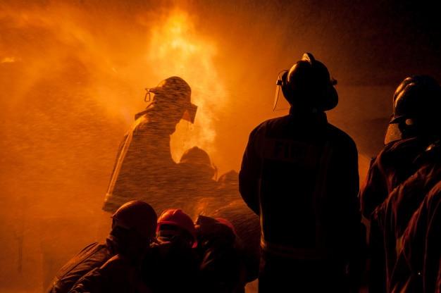 Schattenbild von den feuerwehrmännern, die ein rasendes feuer mit enormen flammen des brennenden bauholzes kämpfen