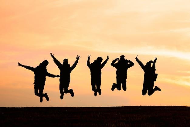 Schattenbild von den freunden, die in sonnenuntergang springen. sport und aktives lebenskonzept