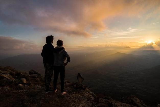 Schattenbild von den liebevollen paaren, die auf dem berg umfassen