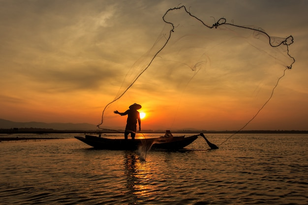 Schattenbild von den traditionellen fischern, die netzfischen inle see zur sonnenaufgangzeit, myanmar werfen