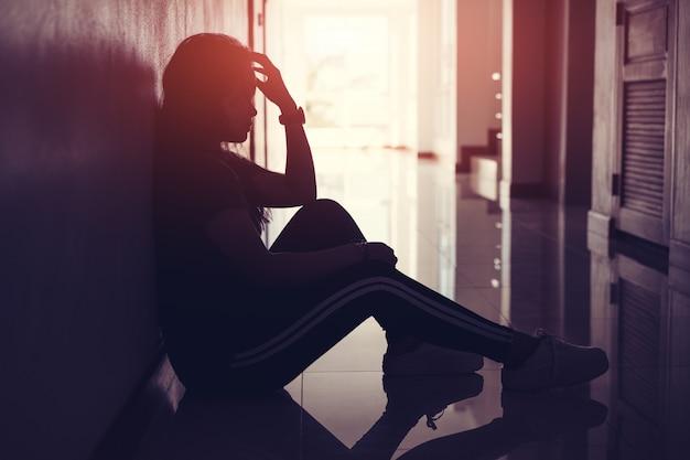 Schattenbild von den traurigen und deprimierten frauen, die am gehweg des kondominiums oder des büros mit hintergrundbeleuchtetem und blendenfleck sitzen
