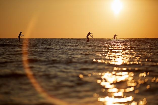 Schattenbild von drei jungen leuten, die auf einem surfbrett zum horizont im schönen szenischen sonnenuntergang der hohen see rudern