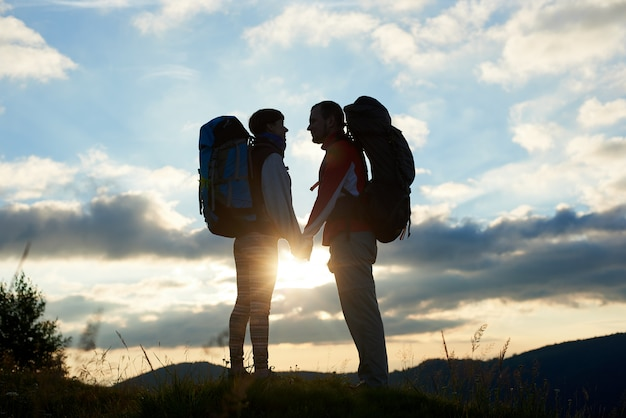 Schattenbild von einigen touristen verliebt in rucksäcke, die einander bei sonnenuntergang in den bergen mit einer landschaft von bergen und bewölktem himmel gegenüberstehen