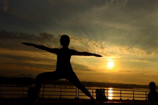 Schattenbild von frauenzug yoga auf rasenyard entlang fluss-berg während des sonnenaufgangs