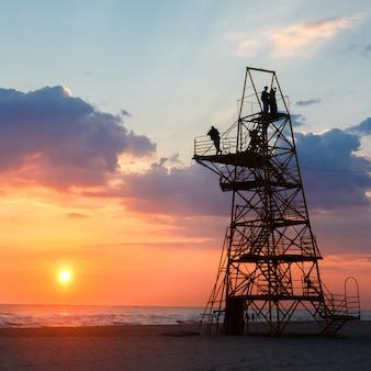Schattenbild von leuten auf einem rettungsturm auf einem sandigen strand bei sonnenuntergang.