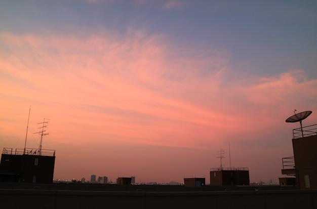 Schattenbild von modernen gebäude-dachspitzen und von satellitenschüssel mit rosa und blauem himmel im hintergrund