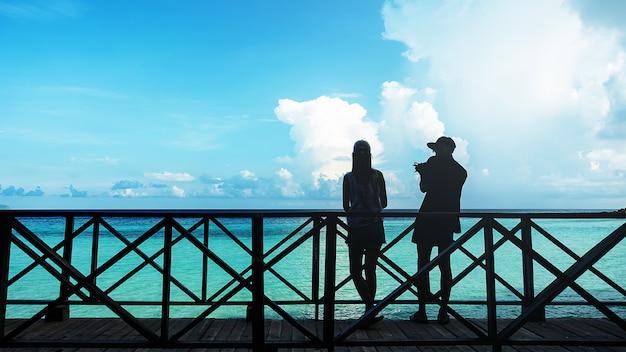Schattenbild von paaren auf der hölzernen terrasse an der küste und am himmel