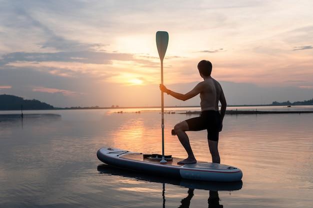 Schattenbild von stehen oben den paddelinternatsschüler, der bei sonnenuntergang auf einem flachen warmen ruhigen fluss schaufelt.