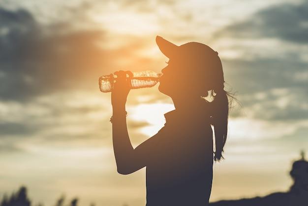Schattenbild von weiblichen berufsgolfern trinken kaltes wasser, um durst zu löschen und die hitze zu entspannen, stehen zwischen spielen, weinlesefarbe still