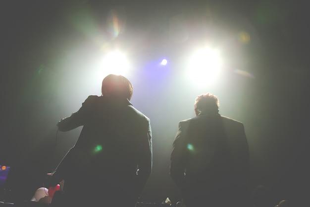 Schattenbild von zwei dj, die an einem konzert durchführen