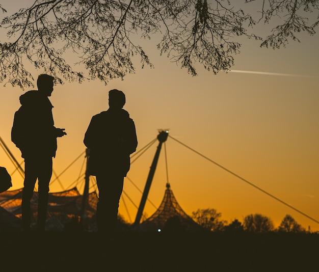 Schattenbild von zwei personen, die unter einem baum während des sonnenuntergangs miteinander sprechen