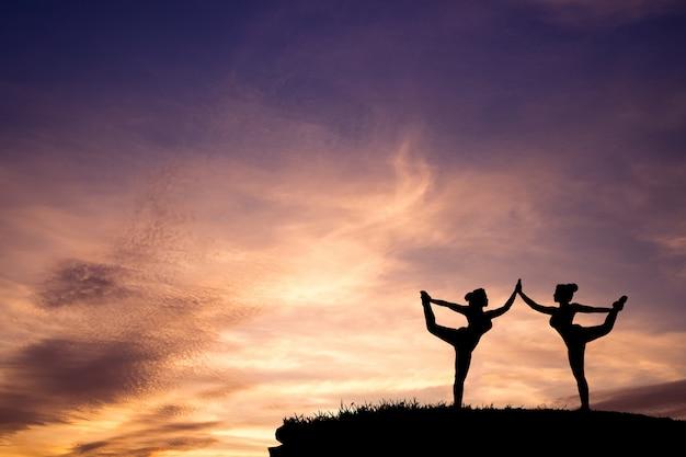 Schattenbild von zwei schönem mädchen yoga stehendem bogen, der haltung auf dem berg mit schönem sonnenunterganghimmel zieht.