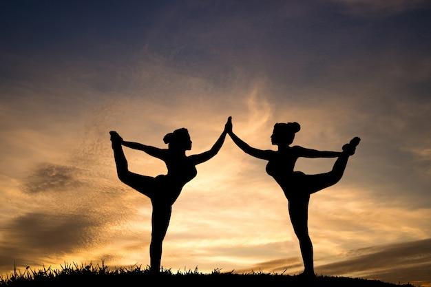 Schattenbild von zwei schönem mädchen yoga stehendem bogen, der haltung im park auf schönem sonnenunterganghimmel zieht.