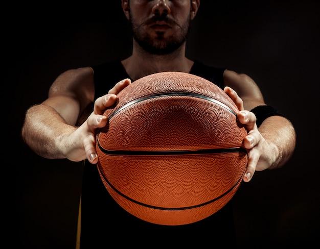 Schattenbildansicht eines basketballspielers, der basketball auf schwarzem hintergrund hält