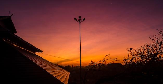 Schattenbildbild des sonnenaufgangs auf dem dach