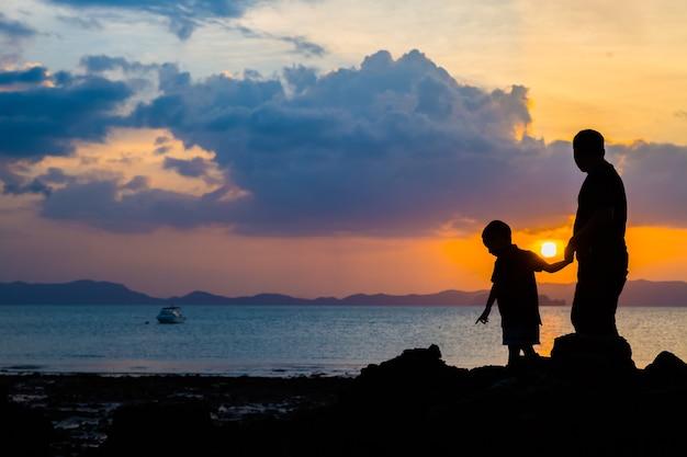 Schattenbildbild des vaters und des sohns am strand vor sonnenunterganghintergrund