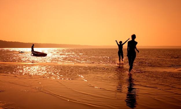 Schattenbildbild von zwei mädchen, die am strand spielen