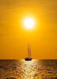 Schattenbildboot im meer und im ozean mit schönem sonnenunterganghimmel