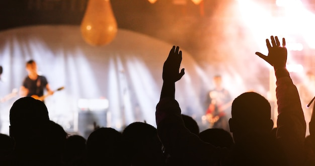Schattenbilder der konzertmasse an der hinteren ansicht der festivalmenge, die ihre hände anhebt