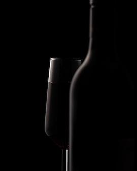 Schattenbilder der weinflasche und des weinglases auf schwarzem