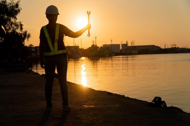 Schattenbilder des asiatischen fraueningenieurs schlüssel halten und auf werft stehen