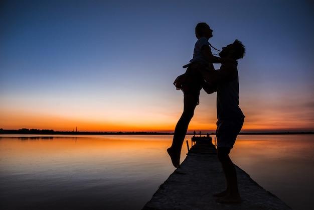 Schattenbilder des jungen schönen paares, das sich am sonnenaufgang nahe see erfreut