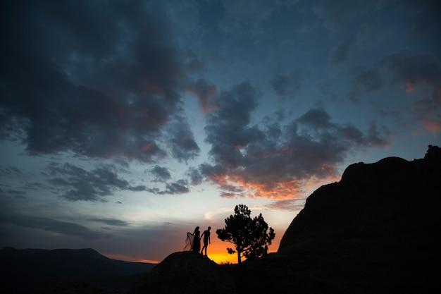 Schattenbilder eines jungen paarliebhabers bei sonnenuntergang in strahlen der untergehenden sonne