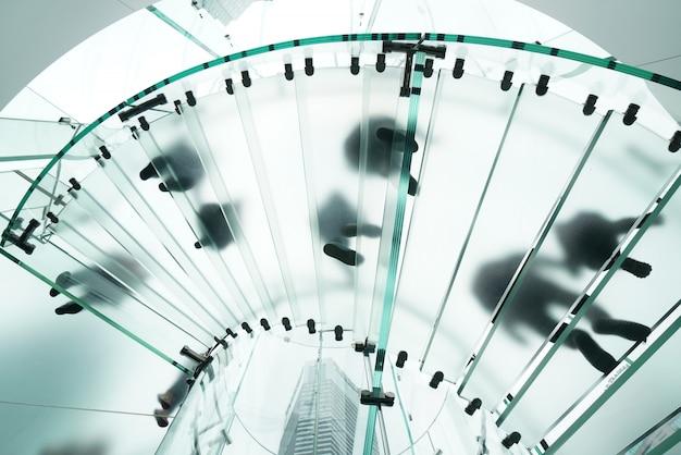 Schattenbilder von den leuten, die auf eine glasspindeltreppe gehen