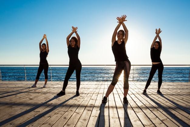 Schattenbilder von sportlichen frauen, die sport nahe meer bei sonnenaufgang tanzen