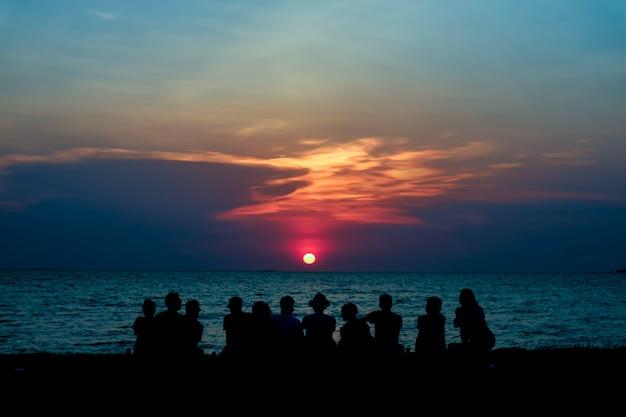 Schattenbildfamilienblick letzten hellen sonnenunterganghimmel auf dem strand