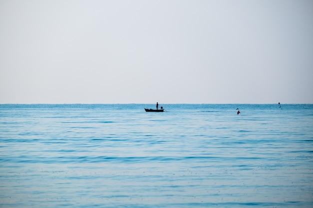 Schattenbildfischer, der das blaue meer schön fischt