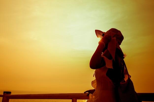 Schattenbildfrauen allein bei sonnenuntergang. traurig und einsam. meer und strand im sommer. reisen und urlaub.
