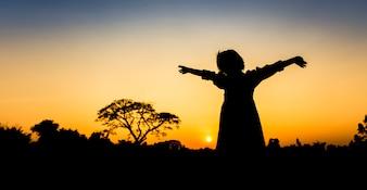 Schattenbildfreiheit ein kleines Mädchen bei Sonnenuntergang