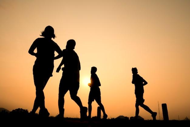 Schattenbildgruppe des jungen gesunden lebensstils, der bei sonnenaufgang läuft