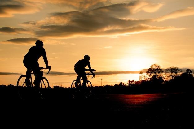 Schattenbildgruppe männer, die fahrrad bei sonnenuntergang fahren.