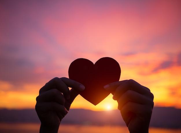 Schattenbildhand, die schönes herz während des sonnenunterganghintergrundes hält. liebe, valentinstag co